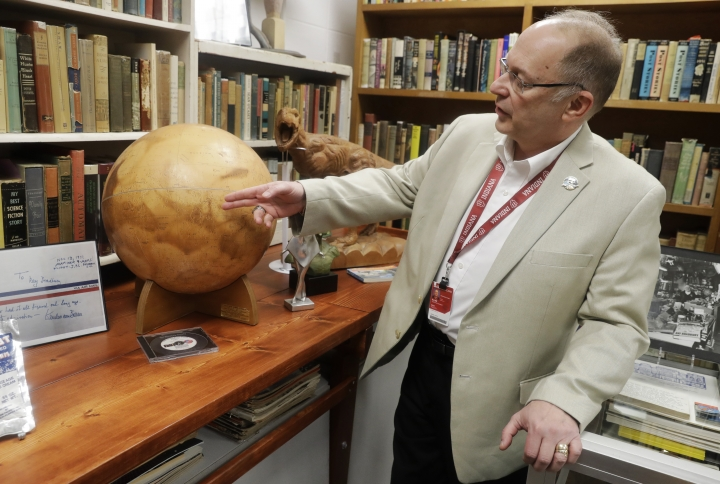 In this Thursday, April 12, 2018, photo, Center for Ray Bradbury Studies director Jonathan Eller points out the location of Gale Crater on the Mars globe, in Indianapolis. The globe presented to Ray Bradbury for his support of NASA's Mariner 9 Mars orbital mission in 1971. (AP Photo/Darron Cummings)