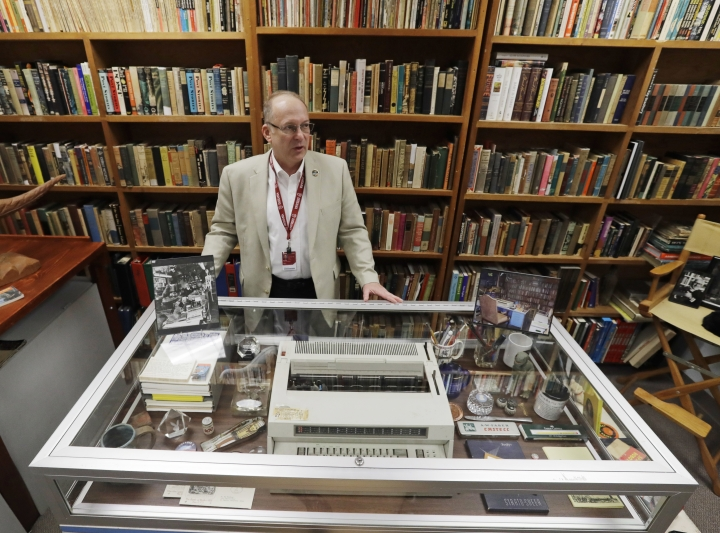 In this Thursday, April 12, 2018, photo, Center for Ray Bradbury Studies director Jonathan Eller stands behind Ray Bradbury's basement office recreation at IUPUI's Center for Ray Bradbury Studies, in Indianapolis. The display includes the author's desk, where Mr. Bradbury worked in his Los Angeles home for nearly half a century. (AP Photo/Darron Cummings)
