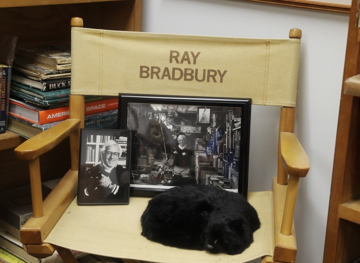 "In this Thursday, April 12, 2018, photo, Ray Bradbury's honorary ""director's chair"" is pictured in Indianapolis. The chair commemorates his close association with the 1983 Disney Studio feature film of his novel, 'Something Wicked This Way Comes.' The imitation cat and publicity photos are a remembrance of ""Tigger,"" his favorite feline. (AP Photo/Darron Cummings)"