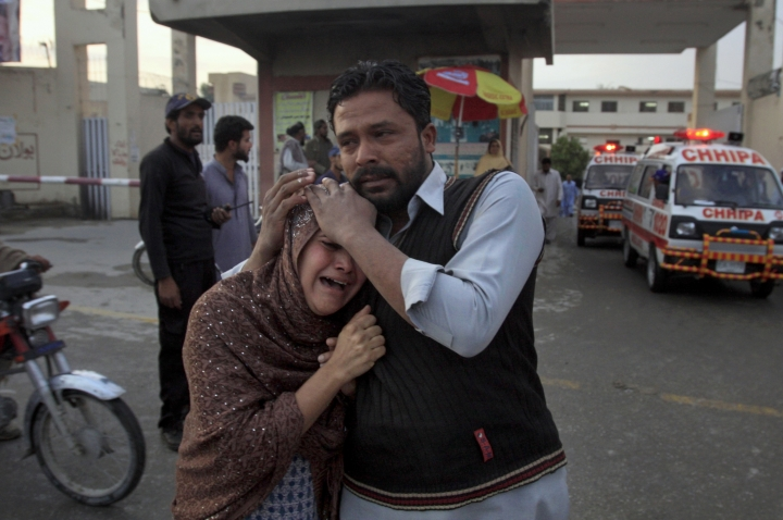 A man comforts a Christian woman who lost her husband in a deadly shooting incident, outside a hospital in Quetta, Pakistan, Sunday, April 15, 2018. Pakistani police say gunmen opened fire on worshippers coming out of a church in the southwestern city of Quetta, killing several people and wounding five others. (AP Photo/Arshad Butt)