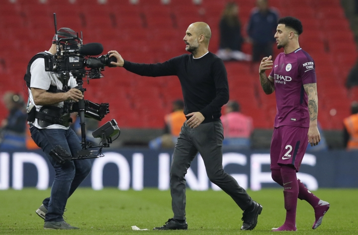 Manchester City coach Pep Guardiola covers a video camera with his hand as he leaves the field with Manchester City's Kyle Walker, right, at the end of the English Premier League soccer match between Tottenham Hotspur and Manchester City at Wembley stadium in London, England, Saturday, April 14, 2018. Manchester City won 3-1. (AP Photo/Tim Ireland)