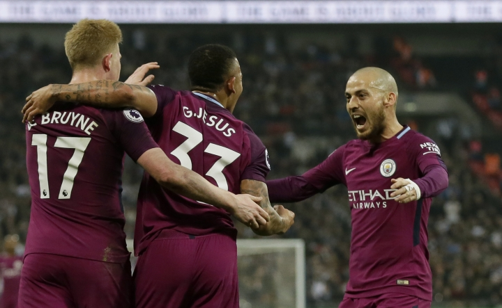 Manchester City's Gabriel Jesus celebrates with Kevin De Bruyne, left, and David Silva, right, after scoring the opening goal during the English Premier League soccer match between Tottenham Hotspur and Manchester City at Wembley stadium in London, England, Saturday, April 14, 2018. (AP Photo/Tim Ireland)
