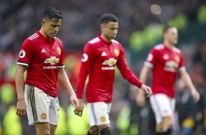Manchester United's Alexis Sanchez, left, leaves the pitch dejected after the final whistle during the English Premier League soccer match against West Bromwich Albion at Old Trafford, Manchester, England, Sunday April 15, 2018. (Nick Potts/PA via AP)