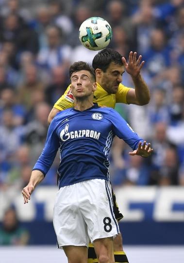 Schalke's Leon Goretzka and Dortmund's Sokratis challenge for the ball during the German Bundesliga soccer match between FC Schalke 04 and Borussia Dortmund in Gelsenkirchen, Germany, Sunday, April 15, 2018. (AP Photo/Martin Meissner)