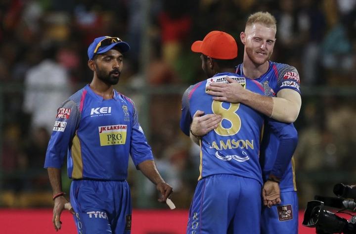 Rajasthan Royals Ben Stokes, right, hugs teammate Sanju Samson as captain Ajinkya Rahane, left, looks on after their win in the VIVO IPL Twenty20 cricket match against Royal Challengers Bangalore in Bangalore, India, Sunday, April 15, 2018. (AP Photo/Aijaz Rahi)