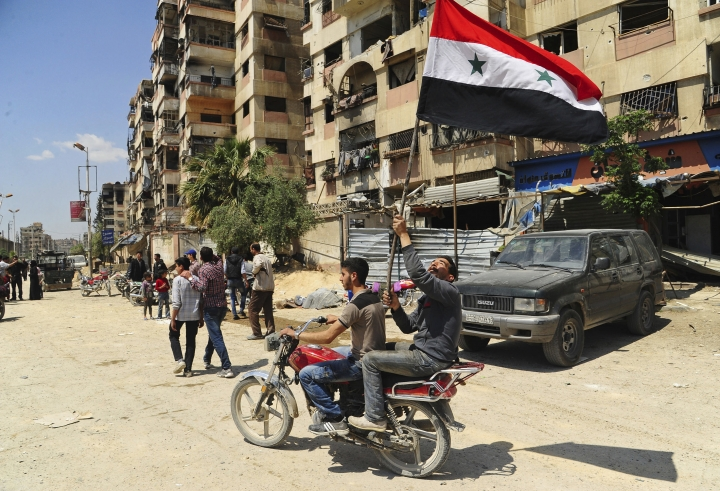 In this photo released Saturday, April 14, 2018, by the Syrian official news agency SANA, Syrian men riding a motorcycle wave their national flag, after Syrian police units entered the town of Douma, the site of a suspected chemical weapons attack and the last rebel-held town in the eastern Ghouta, near Damascus, Syria. Syrian state TV is broadcasting the deployment of 5,000 policemen and internal security in Douma where an alleged chemical attack last weekend triggered unprecedented joint US, British, French strikes in Syria. (SANA via AP)