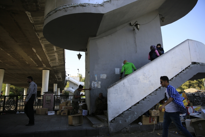 """Syrians walk up stairs of a bridge in Damascus, Syria, Sunday, April 15, 2018. Syria's President Bashar Assad spoke Sunday to a group of visiting Russian politicians saying that Western airstrikes against his country was accompanied by a campaign of """"lies"""" and misinformation in the U.N. Security Council. (AP Photo/Hassan Ammar)"""