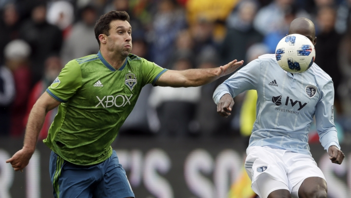 Seattle Sounders defender Will Bruin, left, tries to catch Sporting Kansas City defender Ike Opara, right, during the first half of an MLS soccer match in Kansas City, Kan., Sunday, April 15, 2018. (AP Photo/Orlin Wagner)