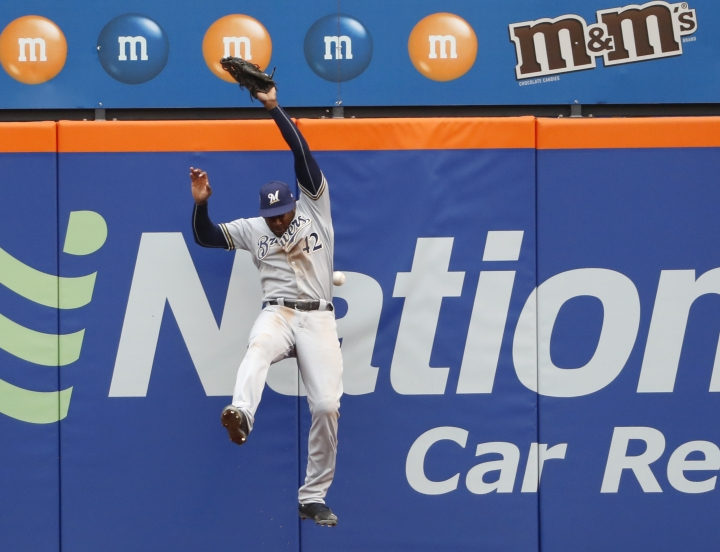 Milwaukee Brewers center fielder Lorenzo Cain (6) leaps but can't get Brandon Nimmo's fourth-inning triple in a baseball game against the New York Mets, Sunday, April 15, 2018, in New York. (AP Photo/Kathy Willens)