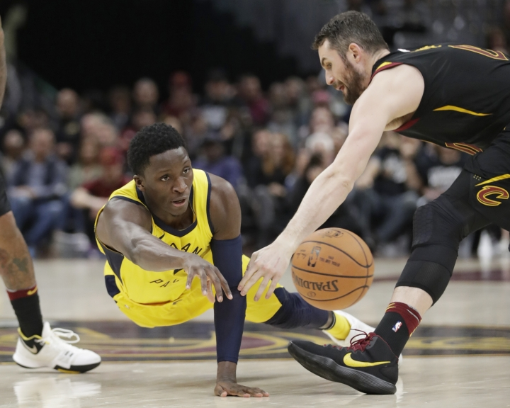 Indiana Pacers' Victor Oladipo, left, passes against Cleveland Cavaliers' Kevin Love in the second half of Game 1 of an NBA basketball first-round playoff series, Sunday, April 15, 2018, in Cleveland. (AP Photo/Tony Dejak)