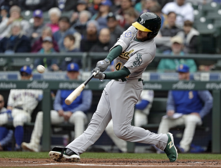 Oakland Athletics' Jed Lowrie connects for a two-run home run against the Seattle Mariners in the first inning during a baseball game Sunday, April 15, 2018, in Seattle. (AP Photo/Elaine Thompson)