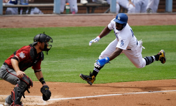 Los Angeles Dodgers' Yasiel Puig, right, scores on a sacrifice fly hit by Enrique Hernandez as Arizona Diamondbacks catcher Jeff Mathis, left, awaits a late throw during the second inning of a baseball game Sunday, April 15, 2018, in Los Angeles. (AP Photo/Mark J. Terrill)