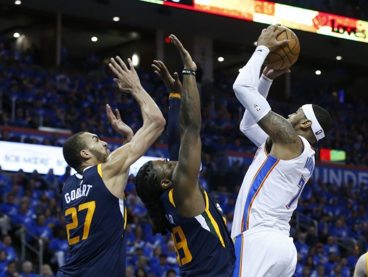 Oklahoma City Thunder forward Carmelo Anthony, right, goes up for a shot as Utah Jazz center Rudy Gobert (27) and forward Jae Crowder (99)stad defend in the first half of Game 1 of an NBA basketball first-round playoff series in Oklahoma City, Sunday, April 15, 2018. (AP Photo/Sue Ogrocki)