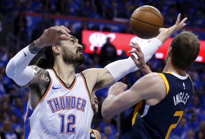 Oklahoma City Thunder center Steven Adams (12) reaches for a rebound with Utah Jazz forward Joe Ingles (2) in the first half of Game 1 of an NBA basketball first-round playoff series in Oklahoma City, Sunday, April 15, 2018. (AP Photo/Sue Ogrocki)