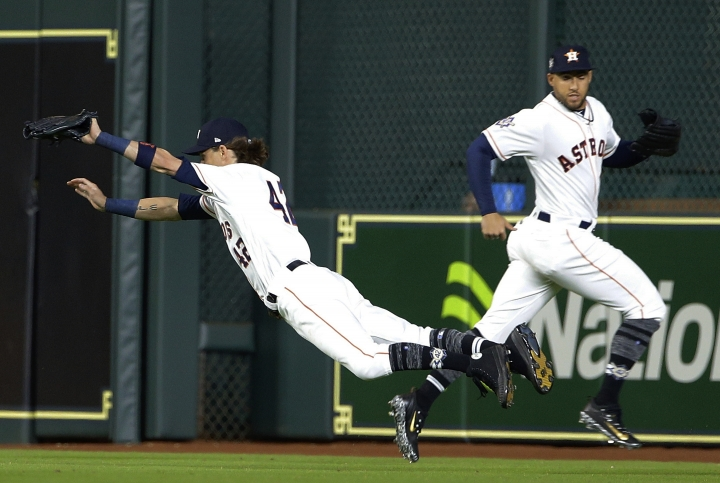 Houston Astros right fielder Josh Reddick, left, makes the catch on a line drive by Texas Rangers' Adrian Beltre as he crosses center fielder George Springer during the seventh inning of a baseball game, Sunday, April 15, 2018, in Houston. Both teams wore No. 42 in honor of Jackie Robinson Day. (AP Photo/Michael Wyke)