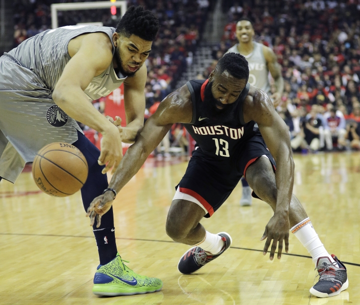 Houston Rockets' James Harden, right, vies for the ball with Minnesota Timberwolves' Karl-Anthony Towns during the first half in Game 1 of a first-round NBA basketball playoff series Sunday, April 15, 2018, in Houston. (AP Photo/David J. Phillip)