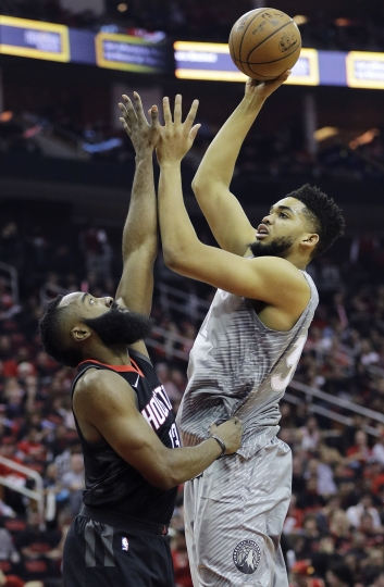 Minnesota Timberwolves' Karl-Anthony Towns shoots over Houston Rockets' James Harden during the first half in Game 1 of a first-round NBA basketball playoff series Sunday, April 15, 2018, in Houston. (AP Photo/David J. Phillip)