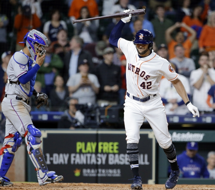 Houston Astros' Jake Marisnick, right, throws down his bat in front of Texas Rangers catcher Robinson Chirinos after striking out on a full count with two on base to end the game with a score of 3-1 in the 10th inning of a baseball game Sunday, April 15, 2018, in Houston. Both teams wore No. 42 in honor of Jackie Robinson Day. (AP Photo/Michael Wyke)