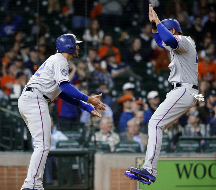 Texas Rangers' Joey Gallo, left, and Ronald Guzman celebrate at the plate after scoring on a double by Robinson Chirinos, making the score 3-1, in the 10th inning of a baseball game against the Houston Astros, Sunday, April 15, 2018, in Houston. Both teams wore No. 42 in honor of Jackie Robinson Day. (AP Photo/Michael Wyke)