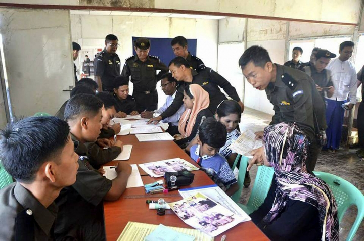 In this April 14, 2018, photo provided by Myanmar Government Information Committee, Myanmar immigration officials examine documents and photographs with a Rohingya family of five at a receiving center in Taung Pyo, Letwe, northern Rakhine state. Myanmar has accepted what appears to be the first five among some 700,000 Rohingya Muslim refugees who fled military-led violence against the minority group, even though the U.N. says it is not yet safe for them to return home. (Myanmar Government Information Committee via AP)