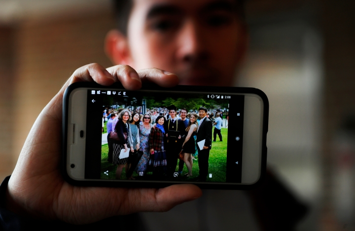 "In this Tuesday, April 10, 2018, photo, Amos Cao, son of Chinese Rev. John Sanqiang Cao, holds a family photo showing his father, far right, in Ann Arbor, Mich. The prominent pastor who has been detained by Chinese authorities since March 5, 2017 was sentenced in March 2018 to seven years in prison for ""organizing others to illegally cross the border."" (AP Photo/Paul Sancya)"