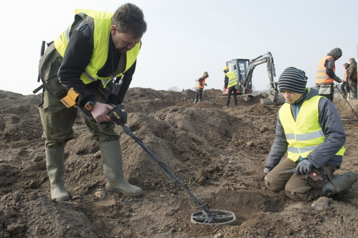 In this April 13, 2018 photo hobby archaeologist Rene Schoen and 13-year-old Luca Malaschnitschenko, right, search for coins after a medieval silver treasure had been found near Schaprode on the northern German island of Ruegen in the Baltic Sea. (Stefan Sauer/dpa via AP)