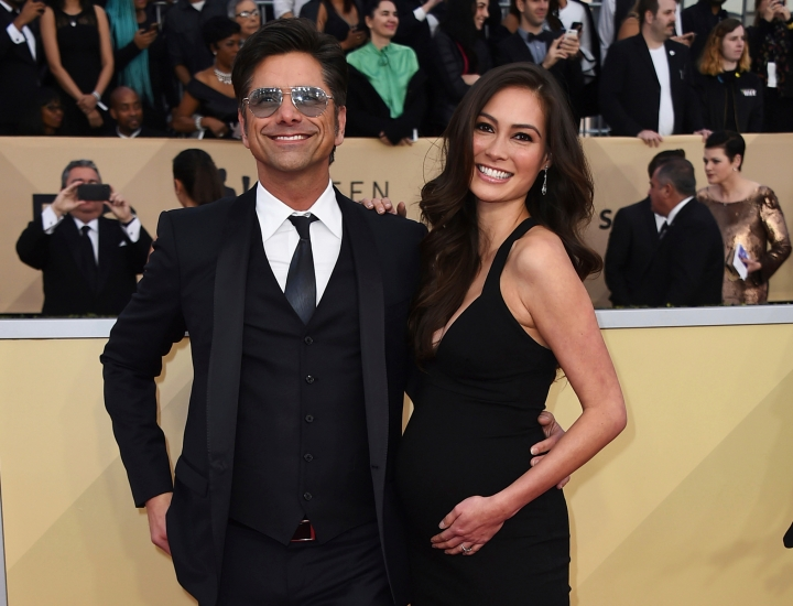 FILE - In this Jan. 21, 2018, file photo, John Stamos, left, and Caitlin McHugh arrive at the 24th annual Screen Actors Guild Awards at the Shrine Auditorium & Expo Hall in Los Angeles. Stamos announced on Instagram the birth of his son, Billy Stamos. (Photo by Jordan Strauss/Invision/AP, File)