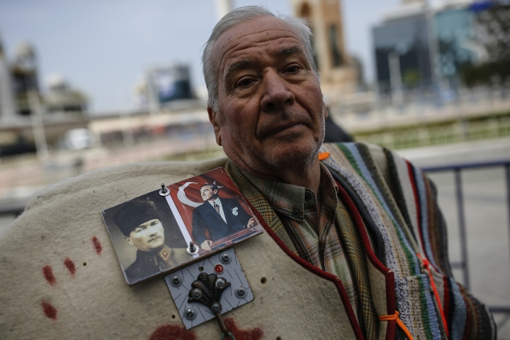 A supporter of Turkey's main opposition Republican People's Party, CHP wearing a jacket decorated with photos of Mustafa Kemal Ataturk, the founder of modern Turkey, takes part in a sit-in protest near central Istanbul's Taksim Square, Monday, April 16, 2018. After it was announced that the motion foreseeing the extension of state of emergency for the seventh time since the failed coup attempt on July 2016, will be discussed in parliament on Wednesday, CHP organised sit-in protests around Turkey calling for the abolishment of the state of emergency. (AP Photo/Emrah Gurel)