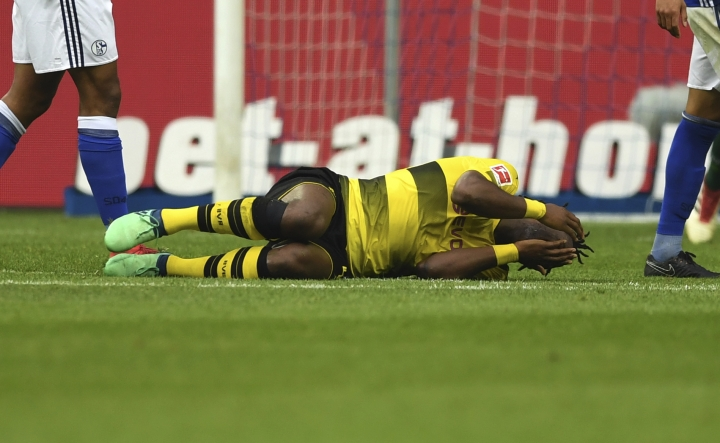 In this April 15, 2018 photo Borussia Dortmund's Michy Batshuayi covers his face in pain during the soccer Bundesliga match between FC Schalke 04 and Borussia Dortmund in Gelsenkirchen, western Germany. Batshuayi's World Cup participation for Belgium is still possible despite suffering an ankle injury in the side's Ruhr derby defeat to Schalke. (Ina Fassbender/dpa via AP)