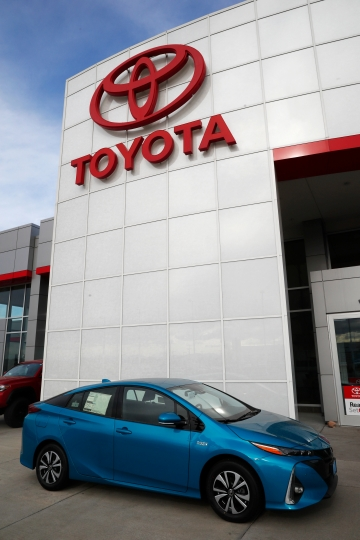 In this Sunday, April 15, 2018, photo an unsold 2018 Prius sits on a Toyota dealer's lot in the south Denver suburb of Englewood, Colo. Toyota says it will start equipping models with technology to talk to other vehicles starting in 2021, as it tries to push safety communications forward. (AP Photo/David Zalubowski)