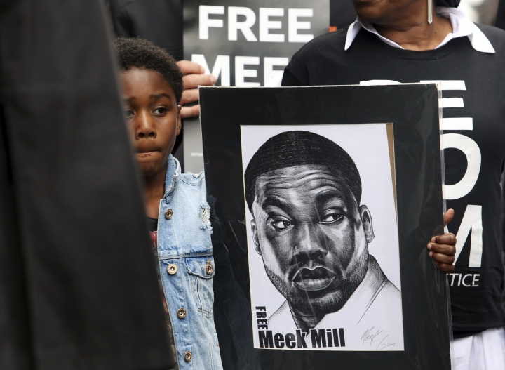 Rapper Meek Mill's son Papi holds a sign as protesters demonstrate in front of a courthouse during a hearing for Meek Mill, Monday April 16, 2018 in Philadelphia. The city's district attorney says Mill's convictions should be vacated and he should have a new trial. The announcement came during a hearing on Monday, but a judge is still refusing to release Mill on bail. Philadelphia-born Mill was sentenced in November 2017 to two to four years in prison for violating probation on a roughly decade-old gun and drug case.(AP Photo/Jacqueline Larma)