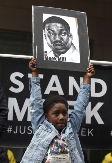 Rapper Meek Mill's son Papi holds a sign as protesters demonstrate in front of a courthouse during a hearing for the rapper, Monday April 16, 2018, in Philadelphia. The city's district attorney says Mill's convictions should be vacated and he should have a new trial. The announcement came during a hearing on Monday, but a judge is still refusing to release him on bail. Philadelphia-born Mill was sentenced in November 2017 to two to four years in prison for violating probation on a roughly decade-old gun and drug case. (AP Photo/Jacqueline Larma)