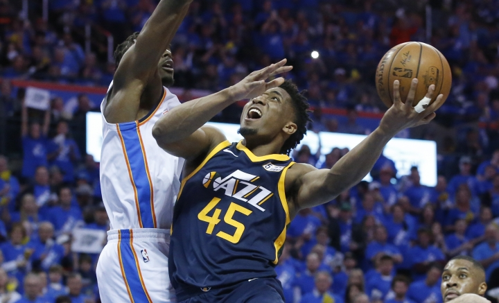 Utah Jazz guard Donovan Mitchell (45) shoots as Oklahoma City Thunder forward Jerami Grant, left, defends in the second half of Game 1 of an NBA basketball first-round playoff series in Oklahoma City, Sunday, April 15, 2018. (AP Photo/Sue Ogrocki)