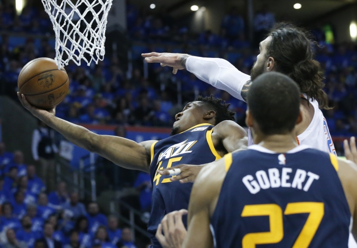 Utah Jazz guard Donovan Mitchell (45) shoots as Oklahoma City Thunder center Steven Adams, right, defends from behind in the second half of Game 1 of an NBA basketball first-round playoff series in Oklahoma City, Sunday, April 15, 2018. (AP Photo/Sue Ogrocki)