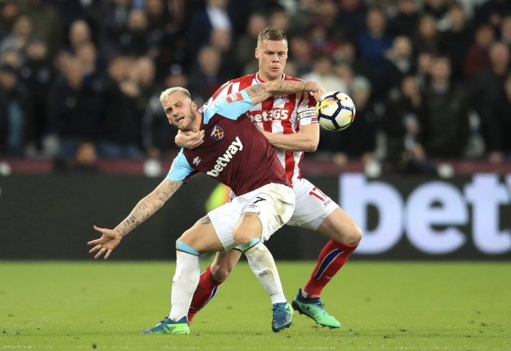 West Ham United's Marko Arnautovic, front, and Stoke City's Ryan Shawcross battle for the ball during the Premier League match at London Stadium Monday April 16, 2018. (Adam Davy/PA via AP)