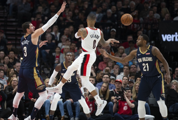 Portland Trail Blazers guard Damian Lillard passes against the defense of New Orleans Pelicans forward Nikola Mirotic, left, and forward Darius Miller during the first half in Game 1 of an NBA basketball first-round playoff series Saturday, April 14, 2018, in Portland, Ore. (AP Photo/Randy L. Rasmussen)