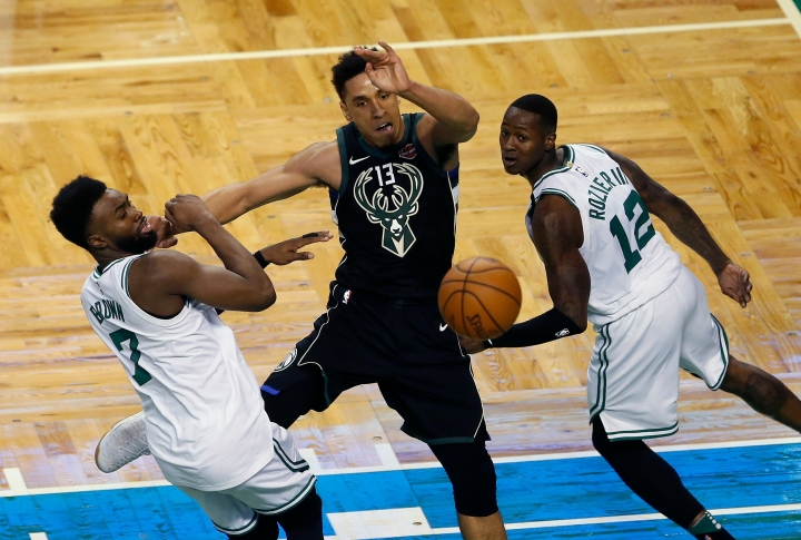 Milwaukee Bucks' Malcolm Brogdon (13) passes off under pressure from Boston Celtics' Jaylen Brown (7) and Terry Rozier (12) during the second quarter of Game 1 of an NBA basketball first-round playoff series in Boston, Sunday, April 15, 2018. (AP Photo/Michael Dwyer)