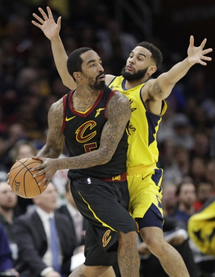 Cleveland Cavaliers' JR Smith, left, looks to pass against Indiana Pacers' Cory Joseph in the second half of Game 1 of an NBA basketball first-round playoff series, Sunday, April 15, 2018, in Cleveland. The Pacers won 98-80. (AP Photo/Tony Dejak)