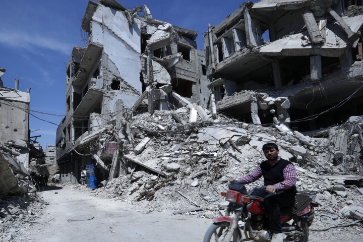 """A man rides past destruction in the town of Douma, the site of a suspected chemical weapons attack, near Damascus, Syria, Monday, April 16, 2018. Faisal Mekdad, Syria's deputy foreign minister, said on Monday that his country is """"fully ready"""" to cooperate with the fact-finding mission from the Organization for the Prohibition of Chemical Weapons that's in Syria to investigate the alleged chemical attack that triggered U.S.-led airstrikes. (AP Photo/Hassan Ammar)"""