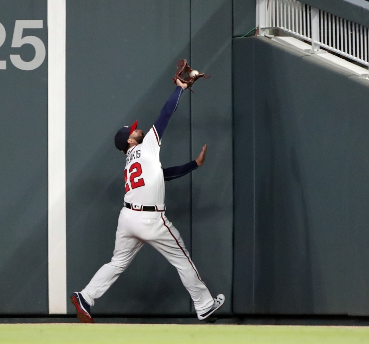 Atlanta Braves right fielder Nick Markakis (22) makes a catches a fly ball at the wall from Philadelphia Phillies catcher Jorge Alfaro in the seventh inning of a baseball game Monday, April 16, 2018, in Atlanta. (AP Photo/John Bazemore)