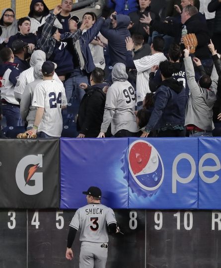 Miami Marlins right fielder J.B. Shuck (3) watches as fans grab at a solo home run by New York Yankees' Aaron Judge during the second inning of a baseball game, Monday, April 16, 2018, in New York. (AP Photo/Julie Jacobson)
