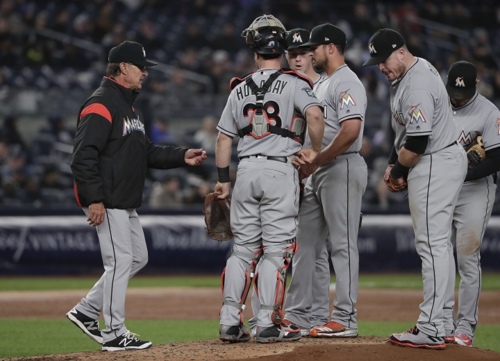 Miami Marlins manager Don Mattingly, left, approaches the mound to relieve pitcher Caleb Smith, center, during the third inning of a baseball game against the New York Yankees, Monday, April 16, 2018, in New York. (AP Photo/Julie Jacobson)