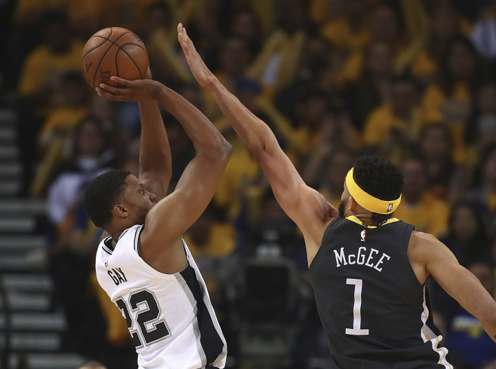 San Antonio Spurs' Rudy Gay, left, shoots against Golden State Warriors' JaVale McGee (1) during the first quarter in Game 2 of a first-round NBA basketball playoff series Monday, April 16, 2018, in Oakland, Calif. (AP Photo/Ben Margot)