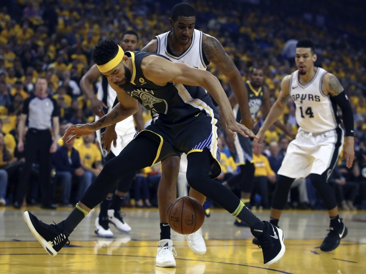 Golden State Warriors' JaVale McGee loses the ball between his legs in front of San Antonio Spurs' LaMarcus Aldridge during the first quarter in Game 2 of a first-round NBA basketball playoff series Monday, April 16, 2018, in Oakland, Calif. (AP Photo/Ben Margot)