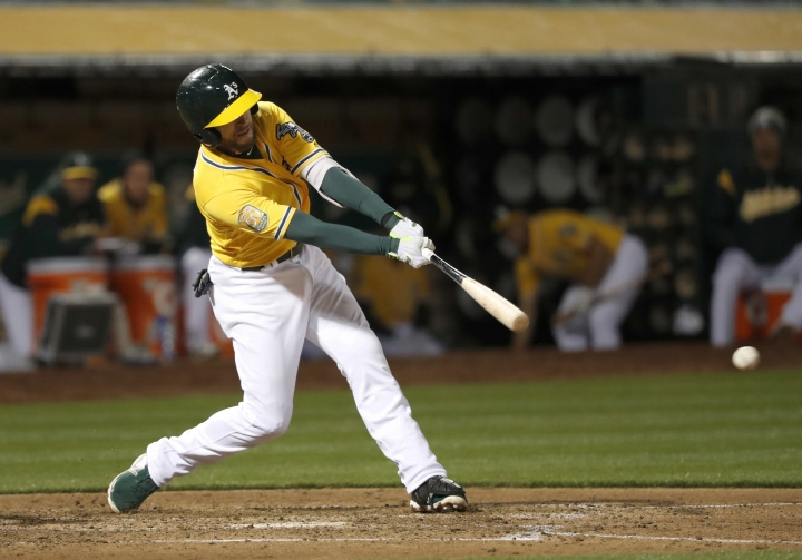 Oakland Athletics' Jed Lowrie hits a single to drive in two runs against the Chicago White Sox during the seventh inning of a baseball game, Monday, April 16, 2018, in Oakland, Calif. (AP Photo/Tony Avelar)