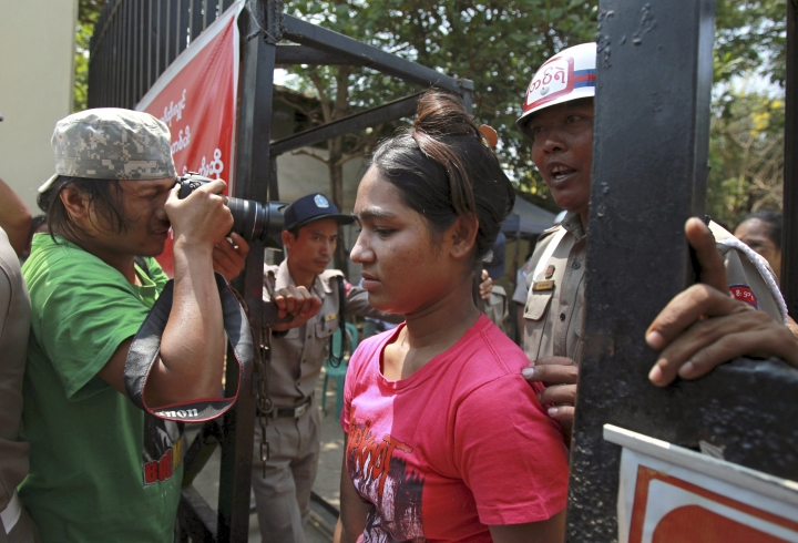 A prisoner, center, passes the entrance gate after she was released from Insein prison Tuesday, April 17, 2018, Yangon, Myanmar. Myanmar President Win Myint has granted amnesty to more than 8,500 prisoners, reportedly including at least three dozen political prisoners. (AP Photo/Thein Zaw)