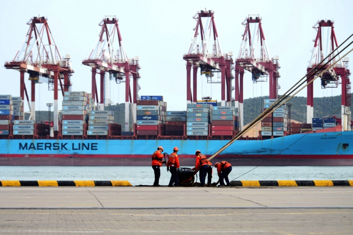 In this Friday, April 13, 2018, photo, workers moor a container ship at the port in Qingdao in eastern China's Shandong province. China's economic growth held steady at 6.8 percent over a year earlier in the quarter ending in March, buoyed by retail sales and investment, data released Tuesday, April 17, 2018. (Chinatopix Via AP)
