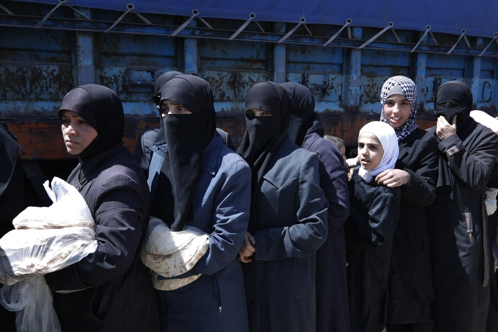 Syrian women wait for Syrian authorities distributing bread, vegetables and pasta to Douma residents, in the town of Douma, the site of a suspected chemical weapons attack, near Damascus, Syria, Monday, April 16, 2018. Two days after Syrian troops declared Douma liberated from opposition fighters, a tour in the city showed the widespread destruction it has suffered since falling under rebel control six years ago. (AP Photo/Hassan Ammar)