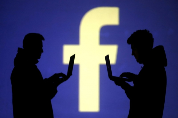 FILE PHOTO: Silhouettes of laptop users are seen next to a screen projection of Facebook logo in this picture illustration taken March 28, 2018.  REUTERS/Dado Ruvic/Illustration