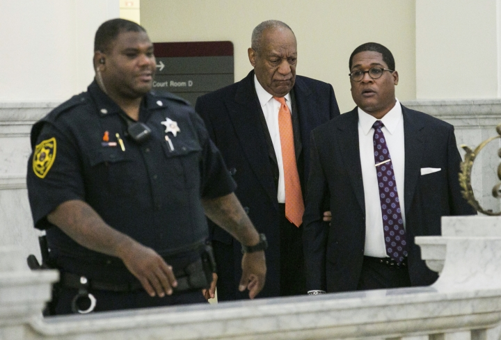 Actor and comedian Bill Cosby, center, and his spokesman Andrew Wyatt, right, proceed towards the courtroom Tuesday, April 17, 2018, during Cosby's sexual assault retrial at the Montgomery County Courthouse, in Norristown, Pa. (Jessica Griffin/The Philadelphia Inquirer via AP, Pool)